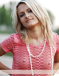Nice blond in the pink blouse and pink panties takes her clothes off and poses on the river beach.