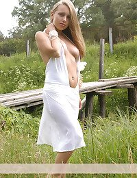 Pricha take off her white glad rags and poses naked on a bridge at one's fingertips the country-side.