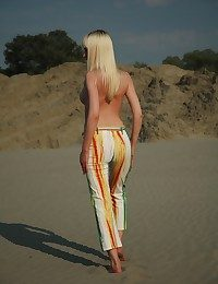 Young and spectacular blonde Aisha object nude on the beach