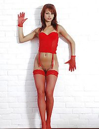 Dispirited redhead with oiled body posing in a gloves and red-hot fishnets